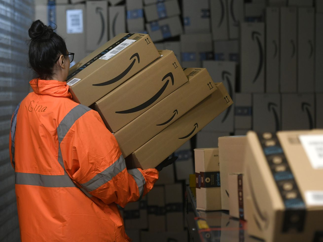 An employee carries a stack of boxes at an Amazon distribution center in Moenchengladbach on December 17, 2019.
