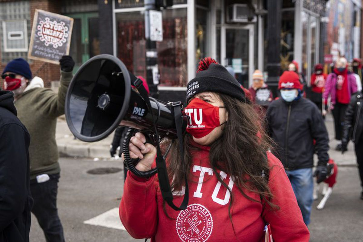 Chicago Teachers Union members and their supporters march Monday in Pilsen after a news conference outside Joseph Jungman Elementary School.