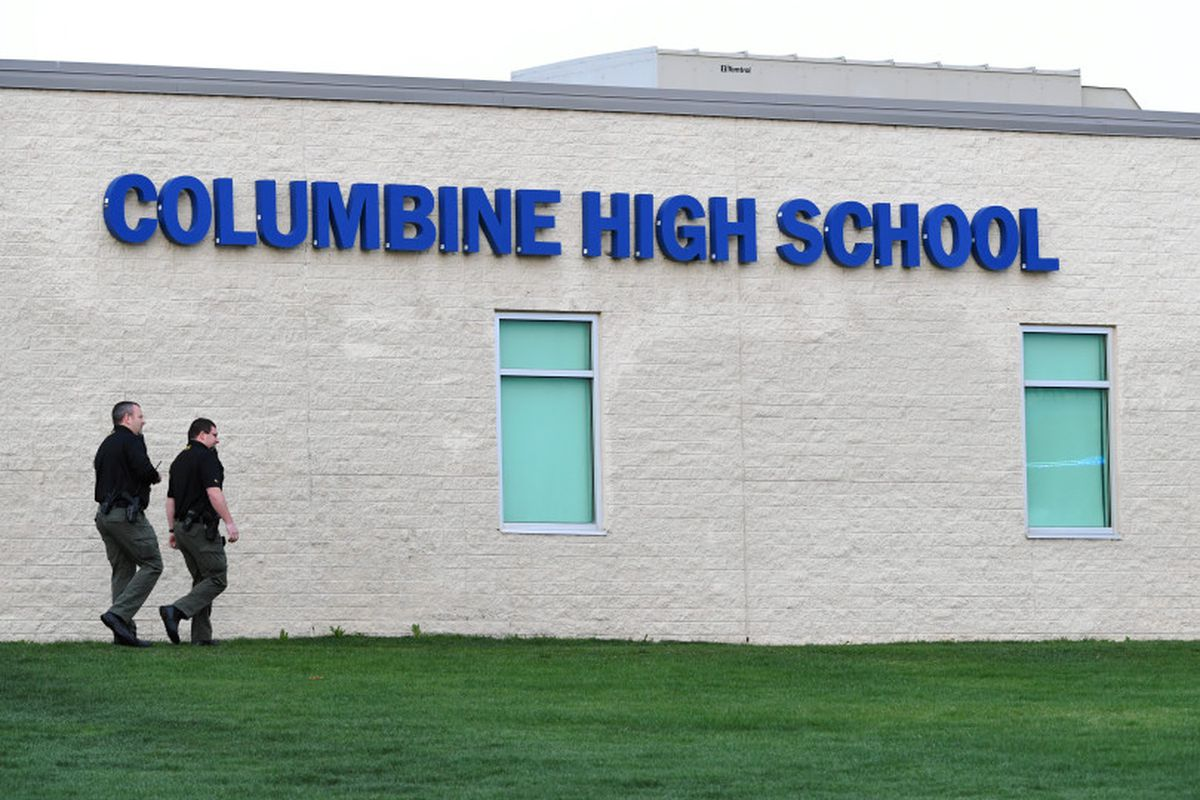 Officers walk around Columbine High School on April 17, 2019, as law enforcement searched for a woman who had traveled from Florida, motivated by an obsession with the 1999 shooting there.