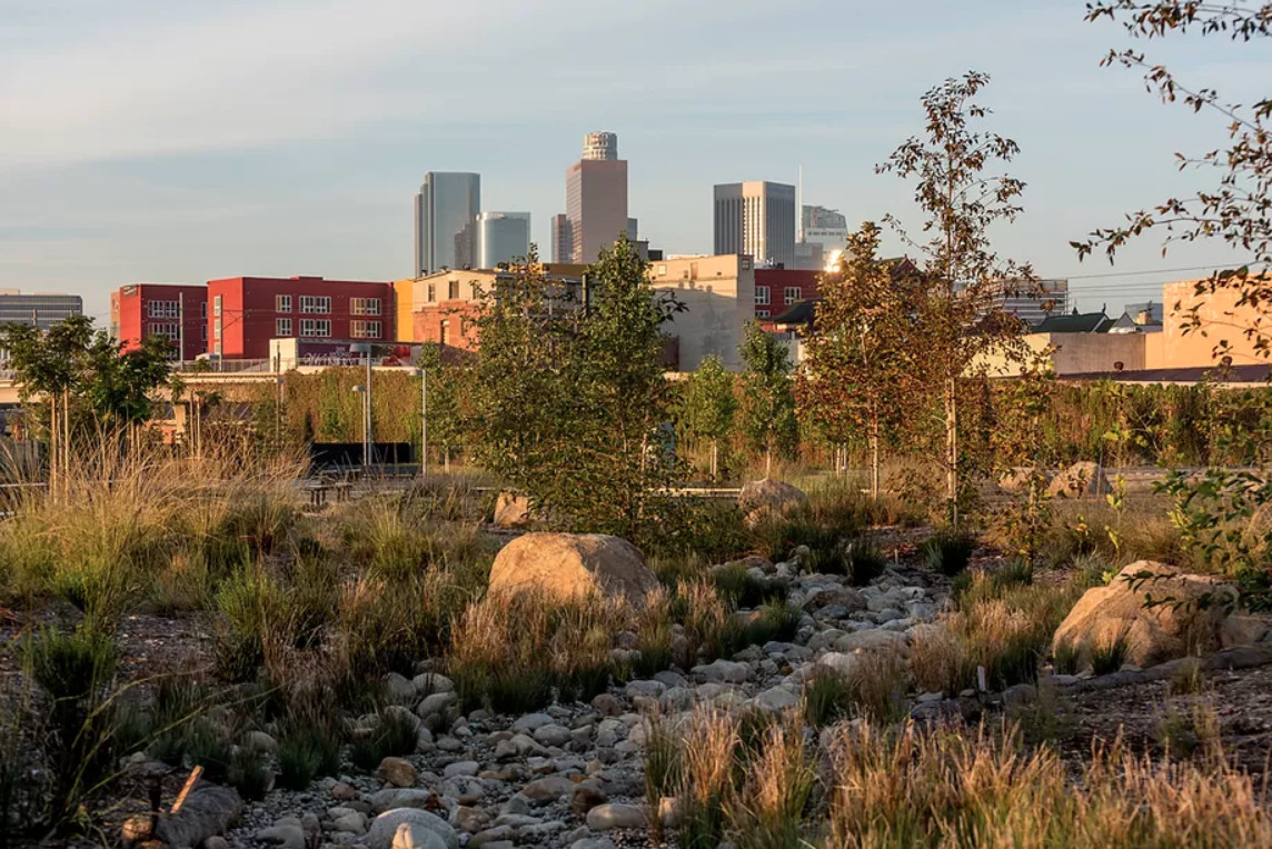 The exterior of Los Angeles State Historic Park. In the foreground are rocks, plants, and trees. In the distance are many city buildings.