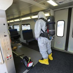 """Responders in chemical suits check a FrontRunner train during """"Hell on Wheels,"""" a full-scale, two-day, emergency protection and response drill at the Salt Lake Central Station on Tuesday, Aug. 8, 2017. The drill included emergency personnel from the Utah Transit Authority, the FBI, Salt Lake County Emergency Management, the West Valley and Salt Lake City fire departments, University of Utah Emergency Management, the University of Utah Police Department, Amtrak, Union Pacific, Murray Victim Advocates and Utah State Medical Examiner's Office. The drill simulated multiple terrorists entering the Salt Lake Valley and dividing up."""