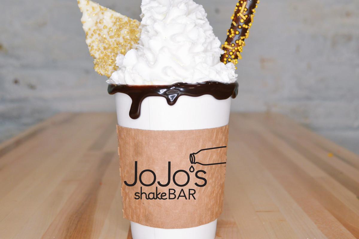A hot chocolate in a cup loaded with whipped cream and a chocolate pretzel.