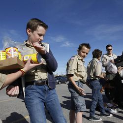 From left, Boy Scouts Luke Beckstrom, Evan Hofheins, Ashton Hofheins and Connor Troxel participate in a food drive assembly line in South Jordan on Saturday, March 21, 2015.