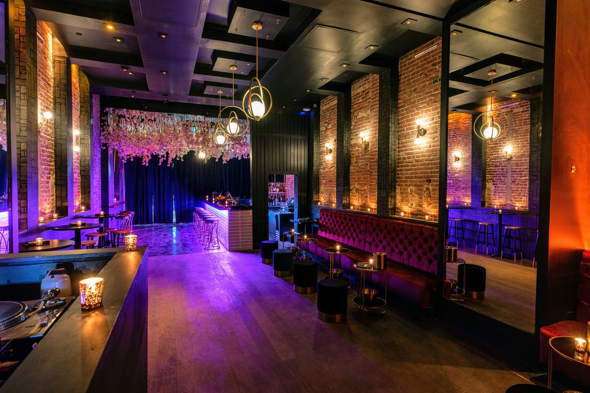dark bar with velvet banquettes, exposed brick walls, and globe lights