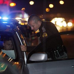 Utah Highway Patrol trooper Wyatt Weber talks with a driver at the scene of a non-injury accident on I-15 on Thursday, Dec. 13, 2012.