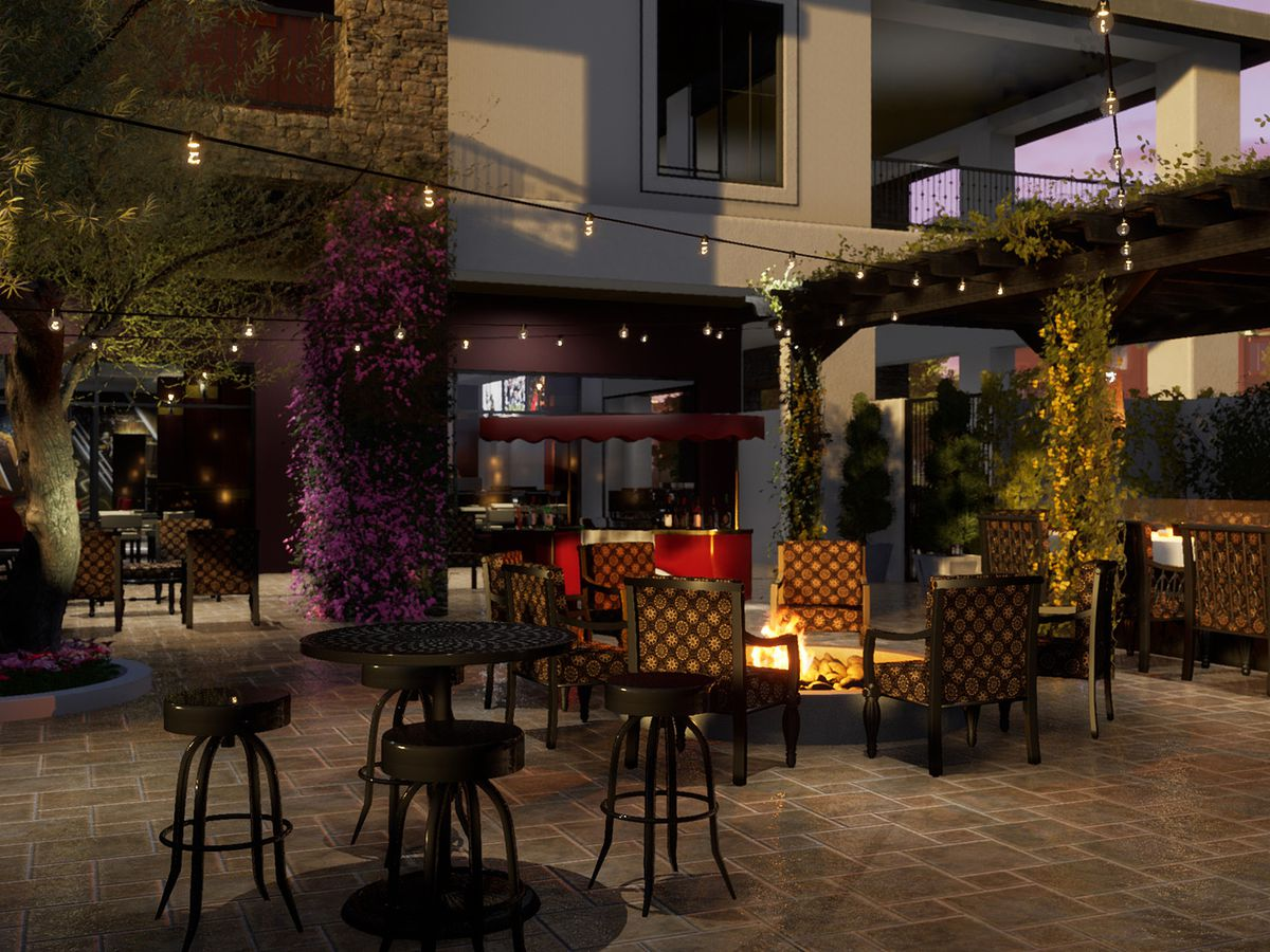 A patio at night with a table and chairs and little lights.