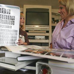 Jenna, 5, and mom Amy Bailey sort items to put in a time capsule for the Oquirrh Mountain Temple at their home in West Jordan on Monday.
