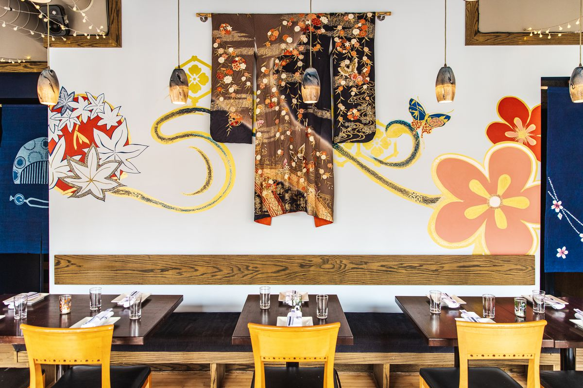 A black and brown kimono decorated with fall leaves hangs on a restaurant wall beside a mural of leaves and flowers.