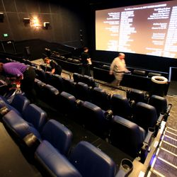 Employees clean the seats, handrails and food trays between movies at the Megaplex Theatres at Jordan Commons in Sandy on Friday, March 13, 2020.