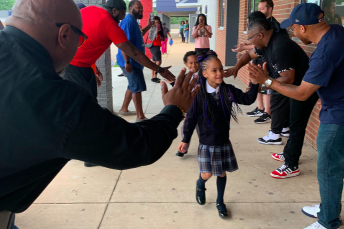 Community members in the Hickory Hill neighborhood offer cheers and high-fives to welcome students back to Power Center Academy Elementary School.
