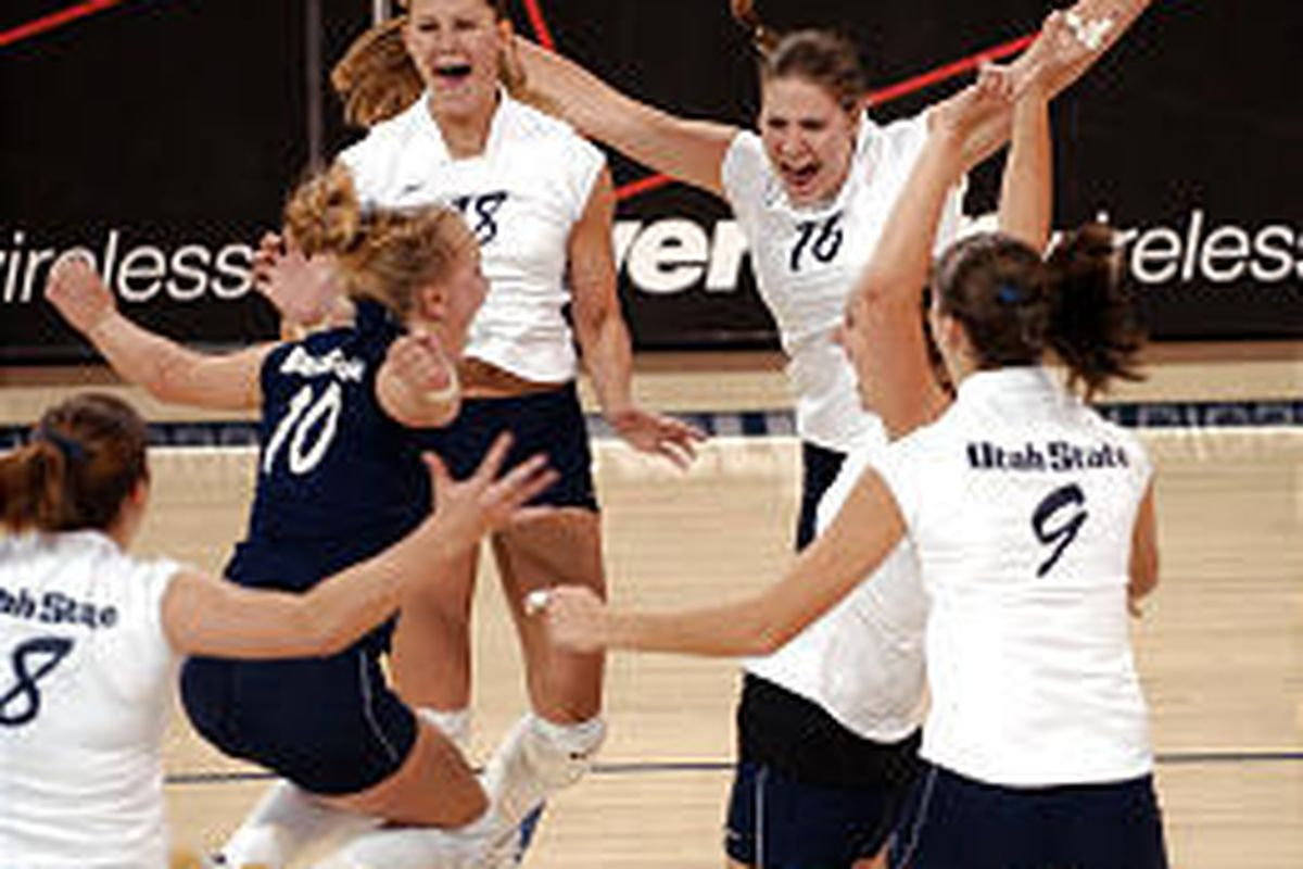 Utah State volleyball players celebrate an unexpected three-game sweep of Utah Tuesday in Logan.