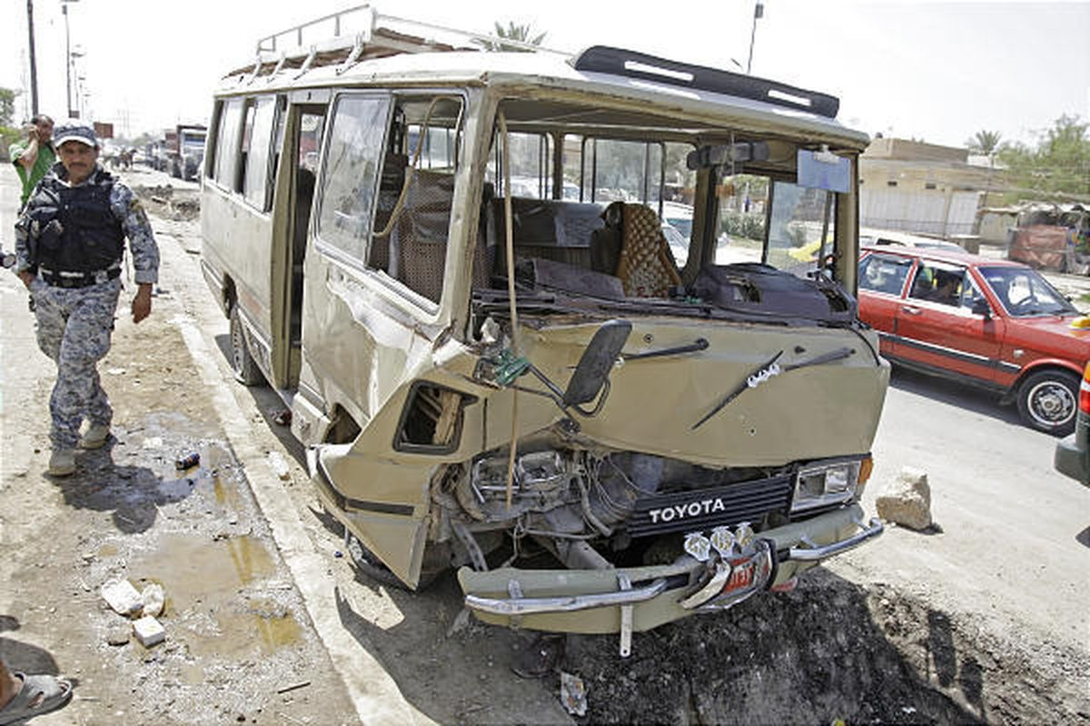A policeman secures the scene of a road side bomb blast that hit a mini bus carrying Shiite pilgrims in Sadr City, in Baghdad, Iraq, Friday.