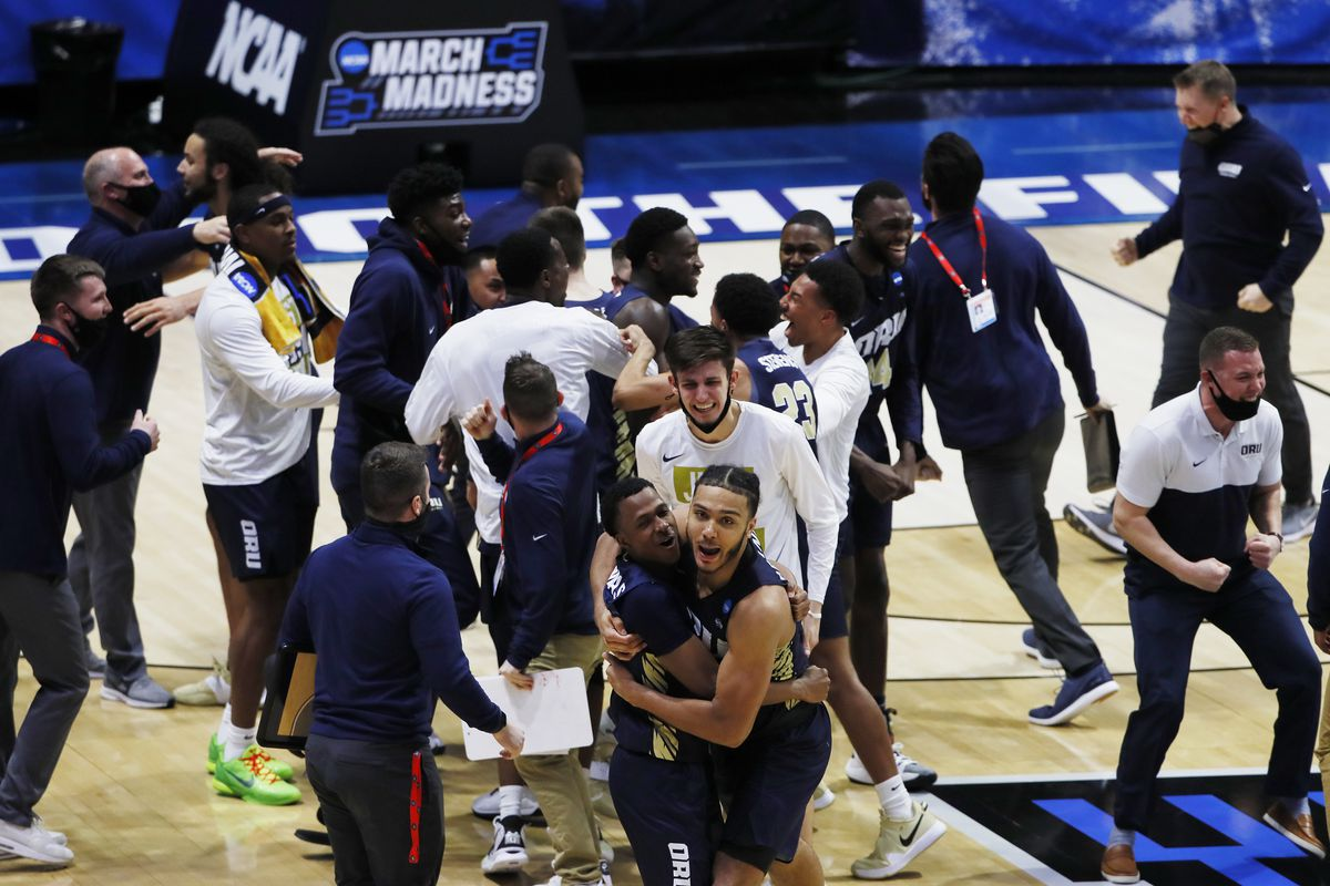 The Oral Roberts Golden Eagles celebrate after an overtime victory against the Ohio State Buckeyes in the first round of the 2021 NCAA Tournament at Mackey Arena.
