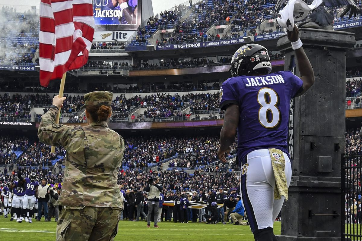 Baltimore Ravens QB Lamar Jackson runs on to the field with a member of the armed services at the start of the Week 11 game against the Houston Texans, Nov. 17, 2019