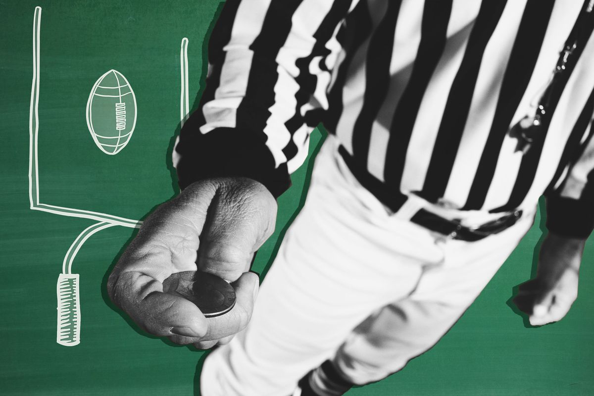 An NFL referee holding a coin