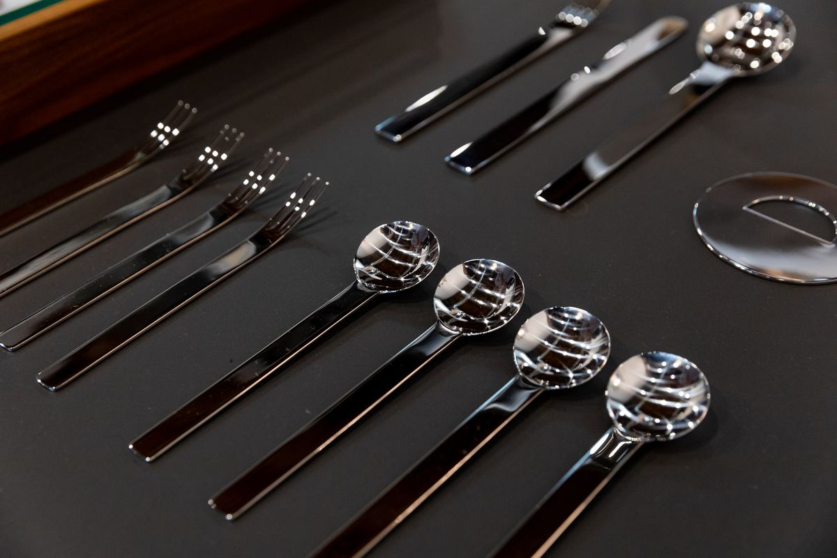 Close-up of four forks with long tines and four spoons with circular cups.