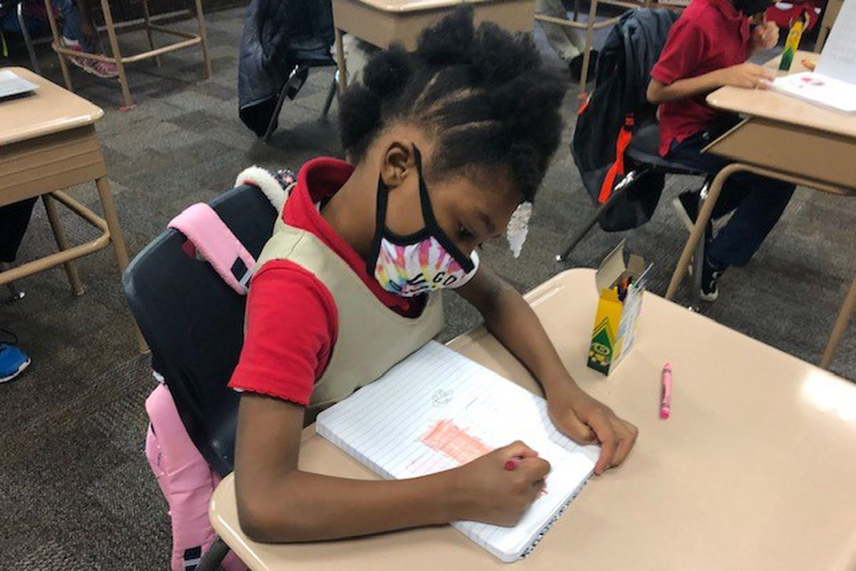 A student wearing a face mask sits at a desk and draws in a notebook with crayons on the first day IPS returned to classrooms during the pandemic.