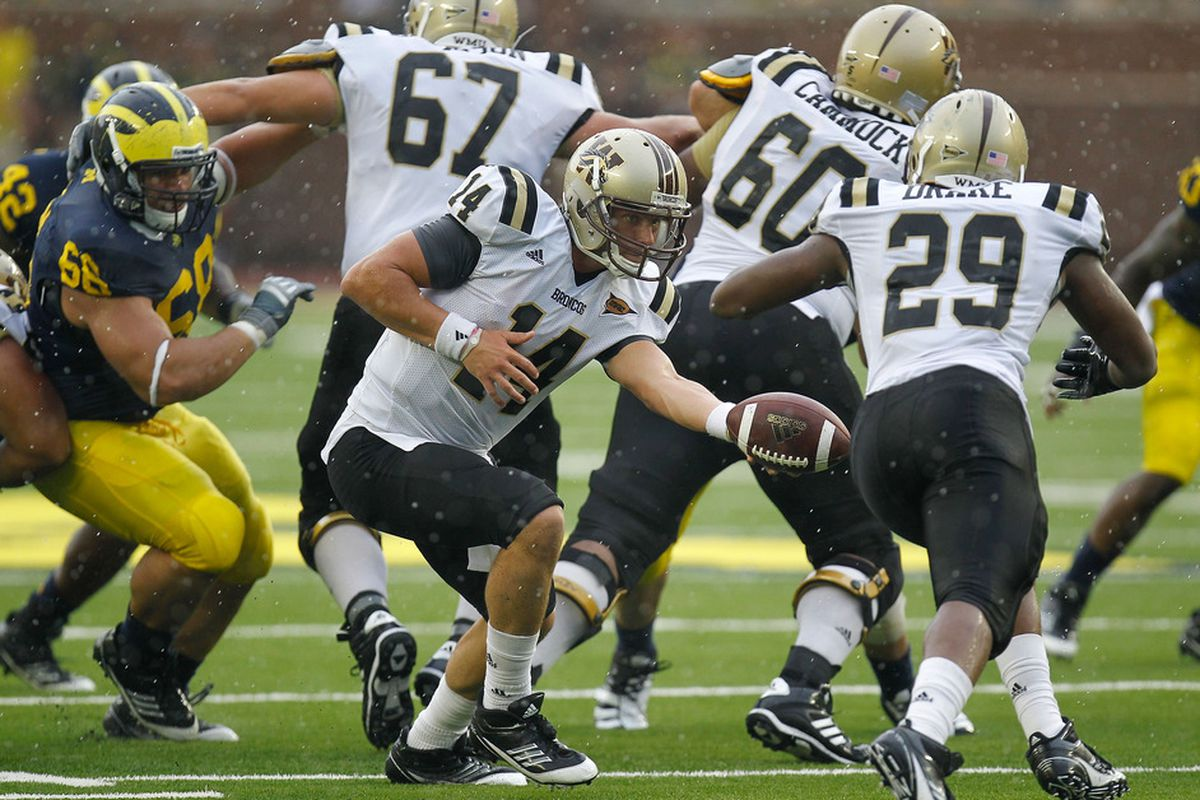 ANN ARBOR, MI - SEPTEMBER 03: Alex Carder #14 of the Western Michigan Broncos hands of to Tevin Drake #29.  (Photo by Gregory Shamus/Getty Images)