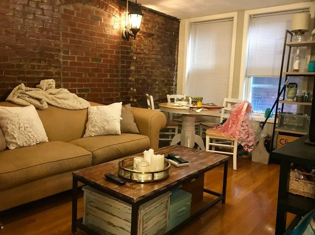 A small living room with furniture, a wall of exposed brick, and two windows.