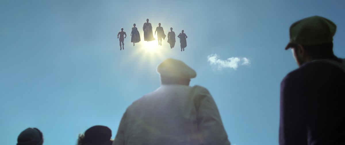 A crowd seen from behind look upward at six hovering superheroes eclipsing the sun in Jupiter's Legacy