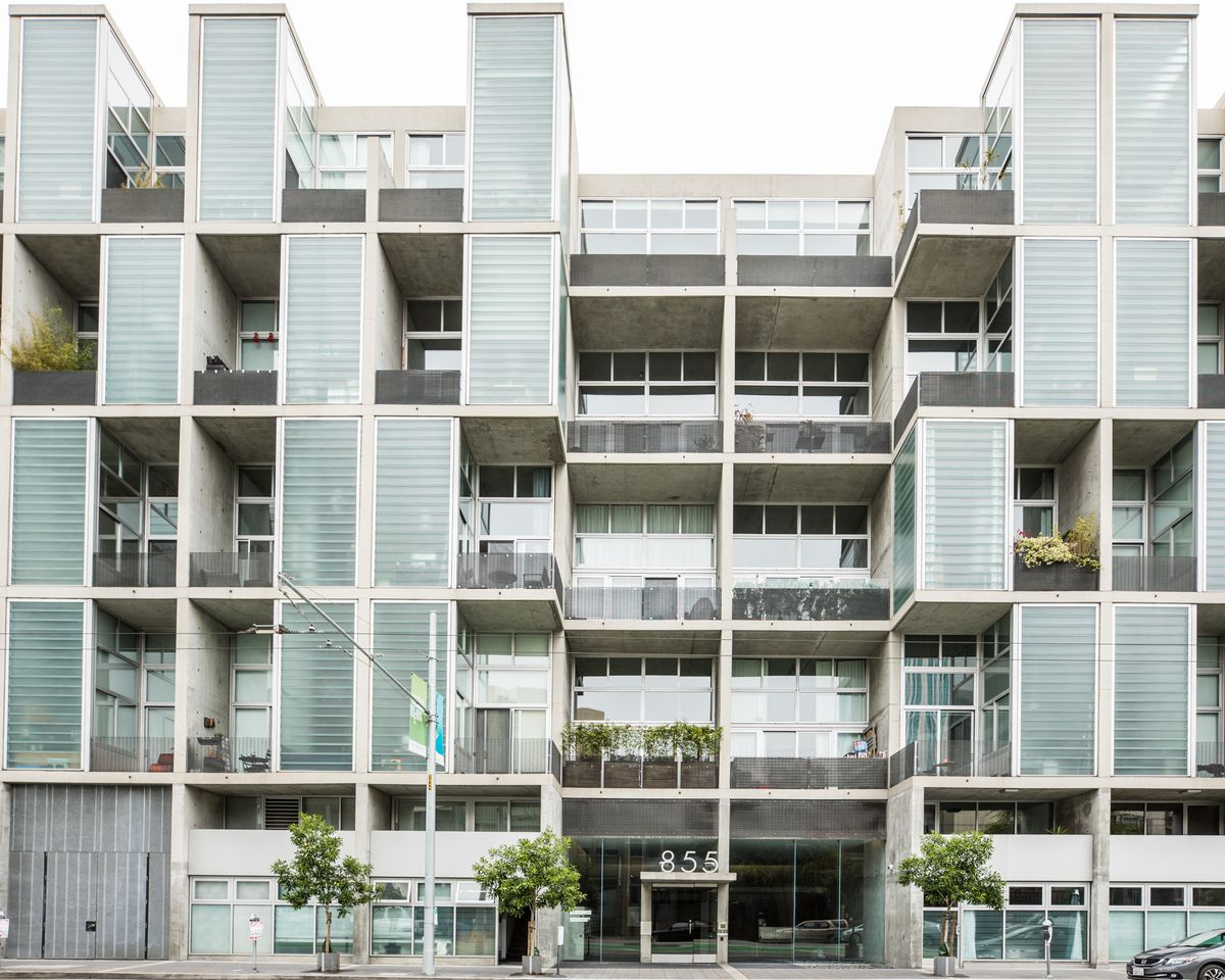 Contemporary residential building with a series of off-center windows made up of opaque glass blocks and balconies with steel railings.