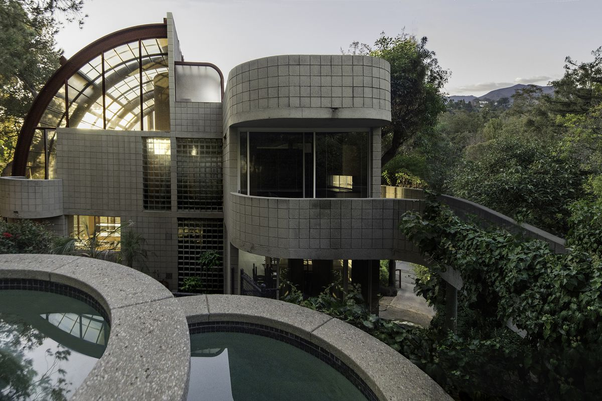 A concrete block house with a portion of the roof entirely made of curving glass panels. A gently curving walkway leads to the house.