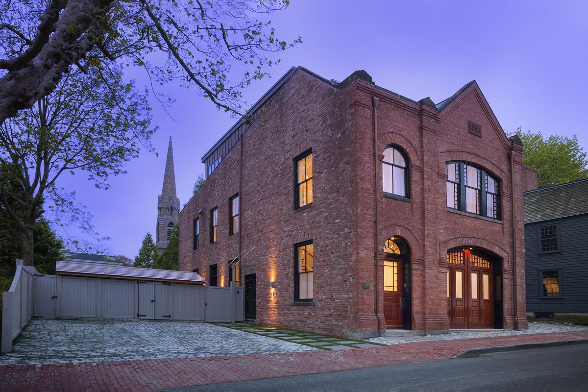 An exterior view of a red brick building with large red door that was formally a fire house and is now a home.