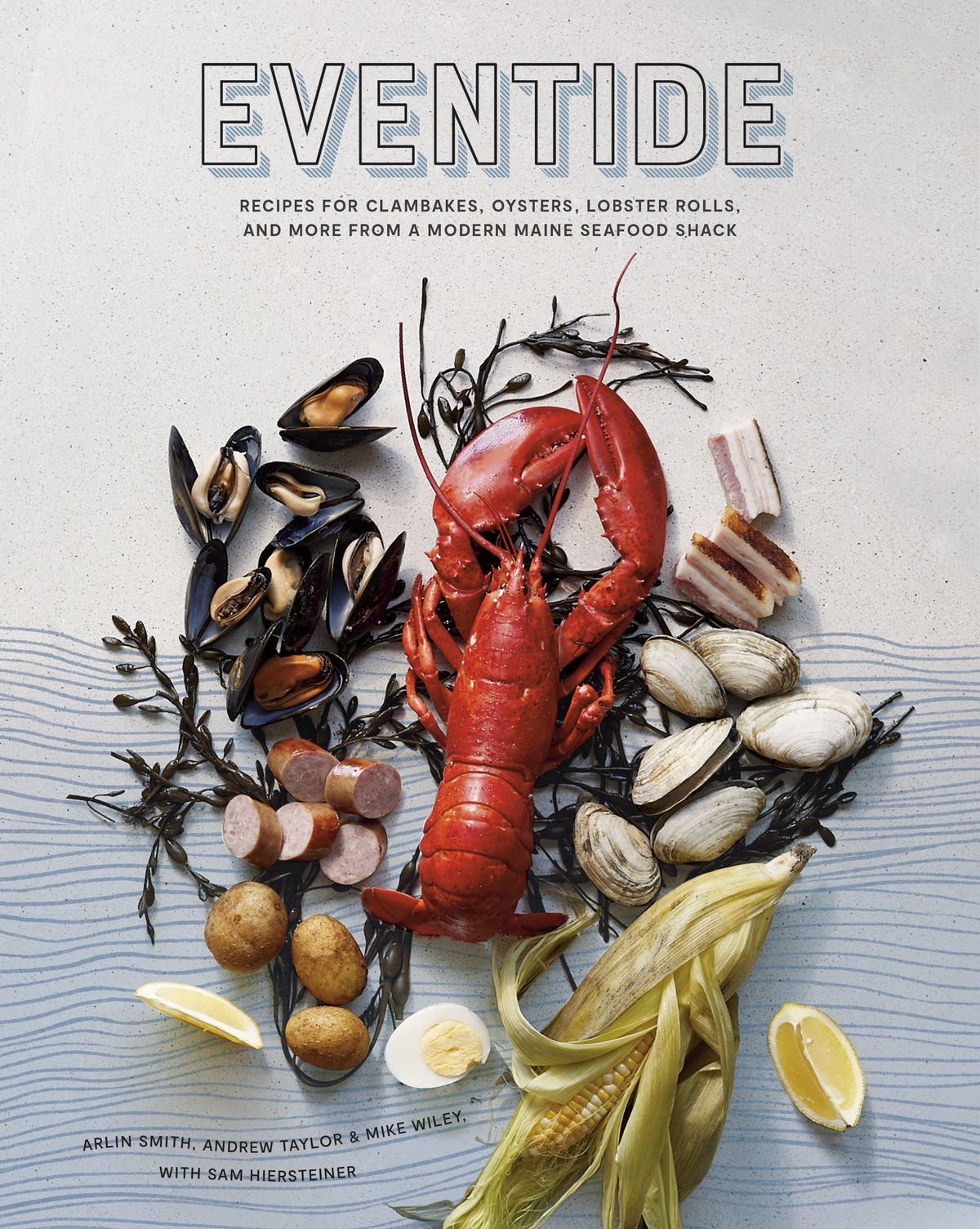 Cover of a cookbook called Eventide: Recipes for Clambakes, Oysters, Lobster Rolls, and More From a Modern Maine Seafood Shack. The cover features a photograph of a lobster, potatoes, sausage, corn, and more ingredients, spread over an ocean-like pattern of blue lines.