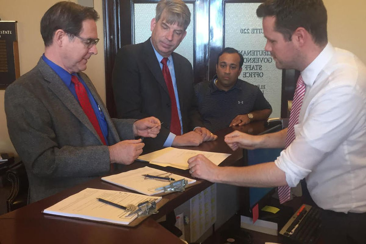 Richard Davis, left, and Jim Bennett submit petitions to register the new United Utah Party with the state elections office on Thursday, May 25, 2017.