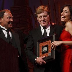"""Governor Gary Herbert and Robert Redford share a laugh as he is presented a gift from Herbert. For all his contributions to the state of Utah, Robert Redford was recognized and honored by Governor Gary Herbert at a gala in his honor, """"The Governor's Salute to Robert Redford: A Utah Tribute to an American Icon"""" at the Grand America Hotel, Saturday, November 9, 2013. Redford is an actor, director, producer, philanthropist, businessman, environmentalist, and founder of the Sundance Resort, the Sundance catalog, and the Sundance Institute which hosts the Sundance Film Festival."""