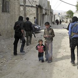 In this Sunday, April 1, 2012 photo, Syrian boys watch Free Syrian Army fighters move through a neighborhood of Damascus, Syria.