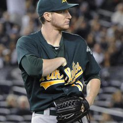 Oakland Athletics starting pitcher Jarrod Parker reaches under his jersey to retrieve the baseball after he caught a ground ball by New York Yankees' Ichiro Suzuki during the third inning of a baseball game Friday, Sept. 21, 2012, at Yankee Stadium in New York. Suzuki singled on the play.