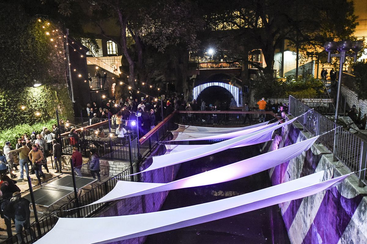 A creek with lighted purple banners stretched from one side to the other