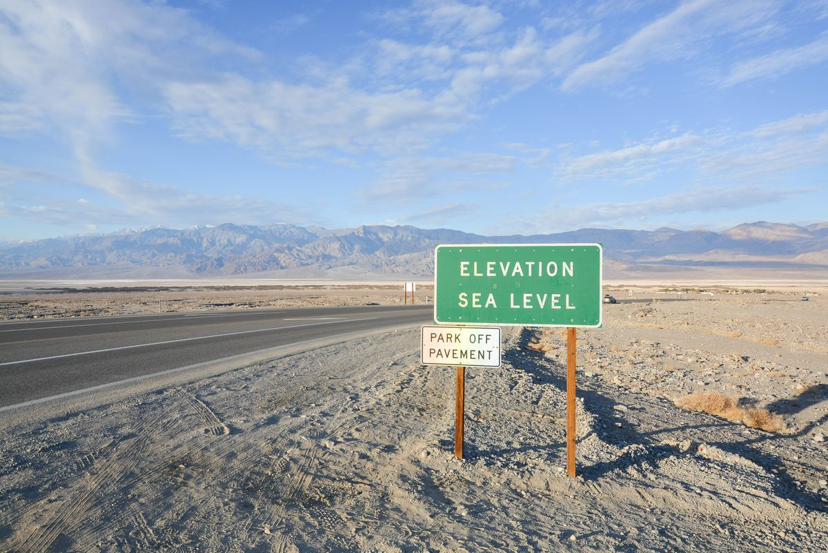 A sign showing sea level elevation in the middle of a wide desert.