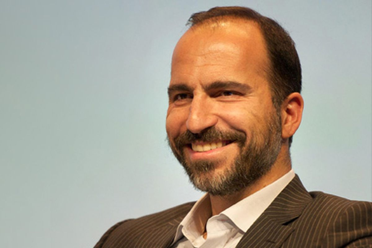 Uber CEO Dara Khosrowshahi sits in front of a gray background.