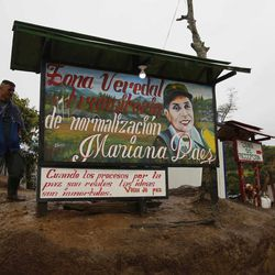 A rebel of the Revolutionary Armed Forces of Colombia, FARC, stands guard at the Mariana Paez demobilization zone, one of many rural camps where rebel fighters are making their transition to civilian life, in Buenavista, Colombia, Monday, June 26, 2017. On Tuesday, Colombia's President Juan Manuel Santos and the FARC's top commander Timochenko will meet here to commemorate the completion of the disarmament process.