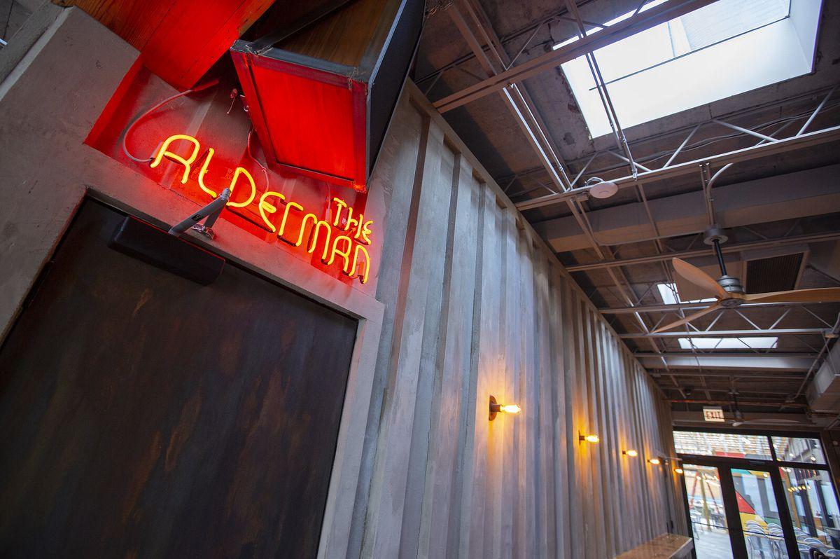 "A red neon sign reads ""The Alderman"" above a dark door in a hallway"