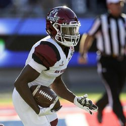 New Mexico State kick-returner Jason Huntley returns a kickoff for a touchdown against Utah State in the first half of the Arizona Bowl NCAA college football game Friday, Dec. 29, 2017, in Tucson, Ariz. (AP Photo/Rick Scuteri)