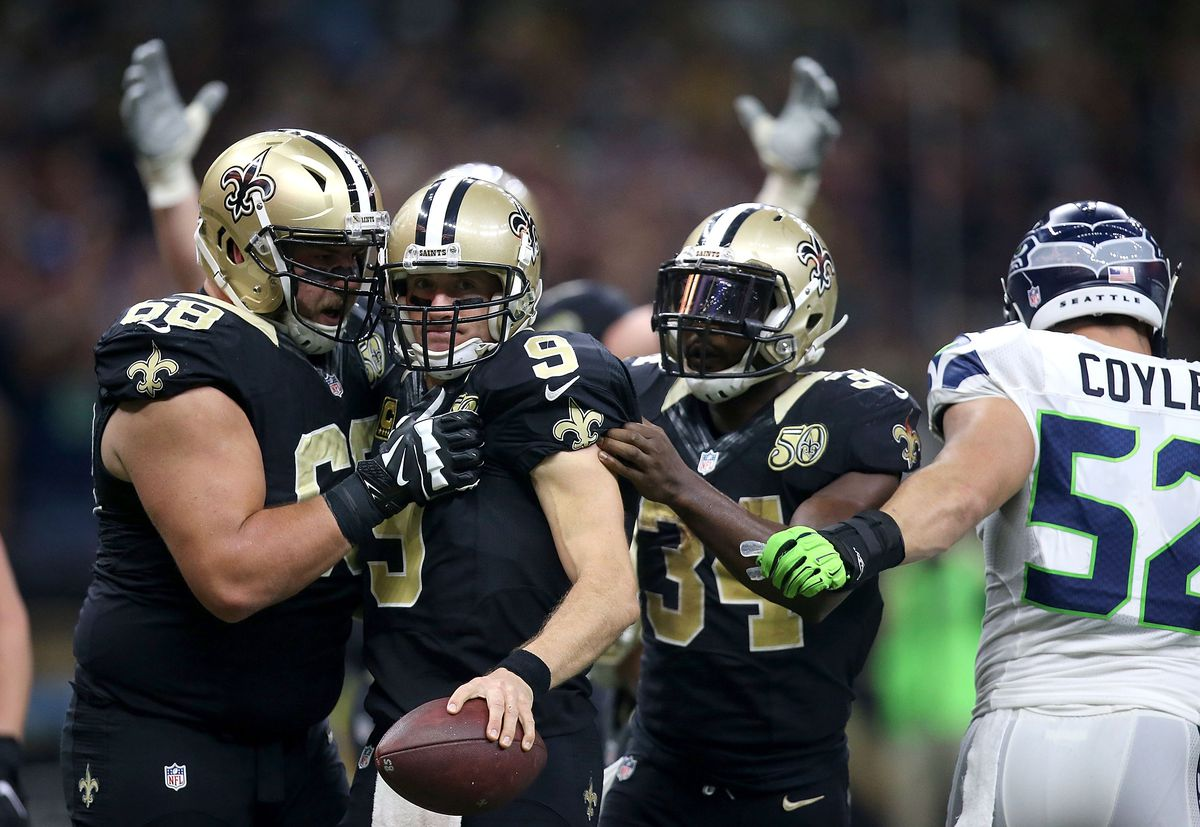 NEW ORLEANS, LA: New Orleans Saints quarterback Drew Brees (9) celebrates with teammates after scoring a touchdown against the Seattle Seahawks defense at the Mercedes-Benz Superdome.