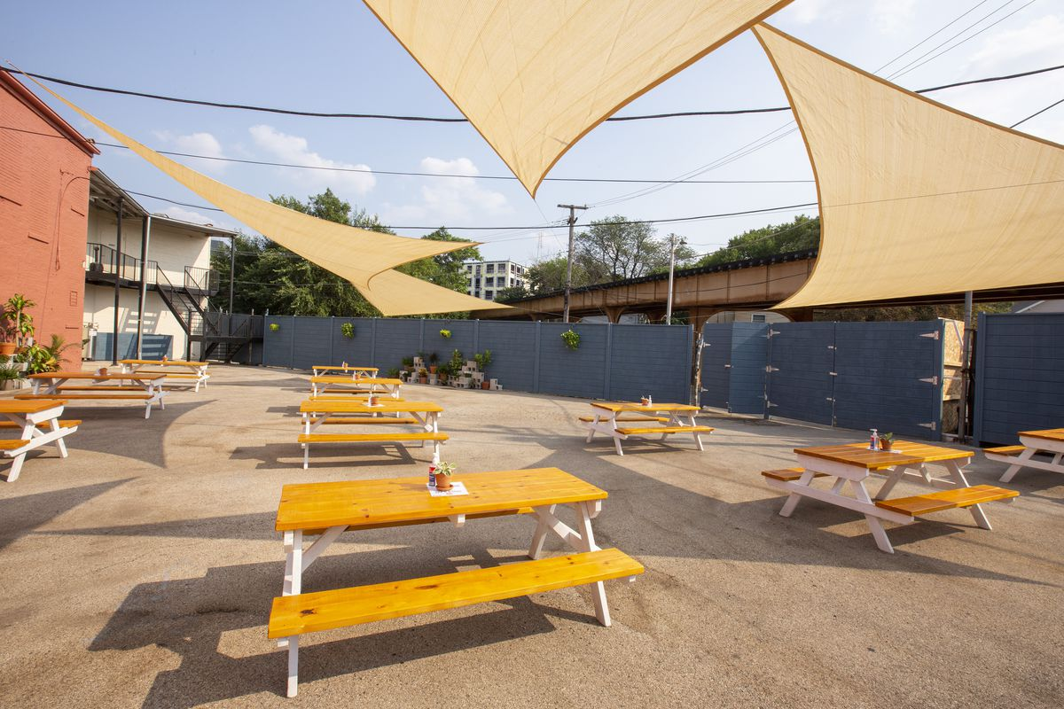 A vacant lot with several picnic tables, and a overhang that protect from the rain.