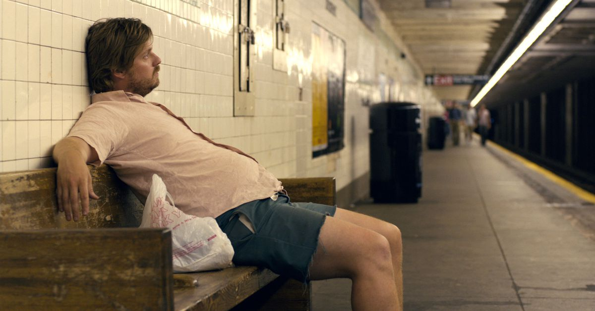 a portly lug in a pink linen shirt and shorts sits waiting for the nyc subway