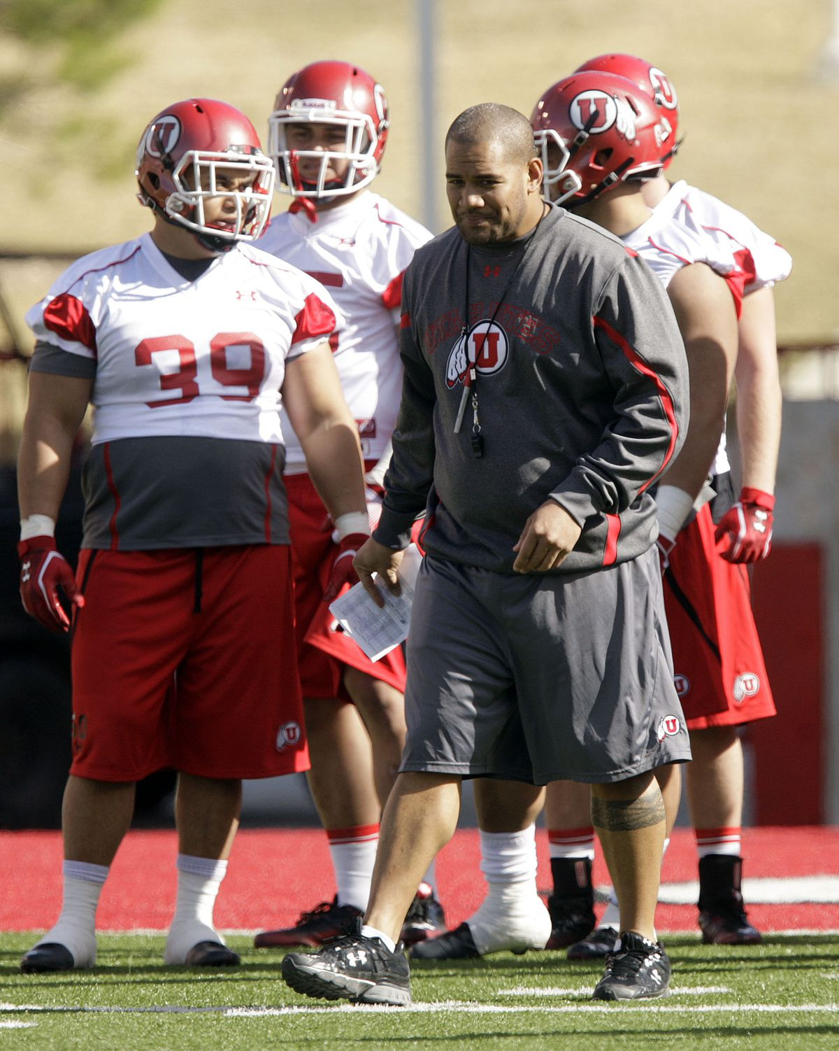 Utah Utes coach Ilaisa Tuiaki works with players in the first spring football practice in Salt Lake City Tuesday, March 20, 2012.