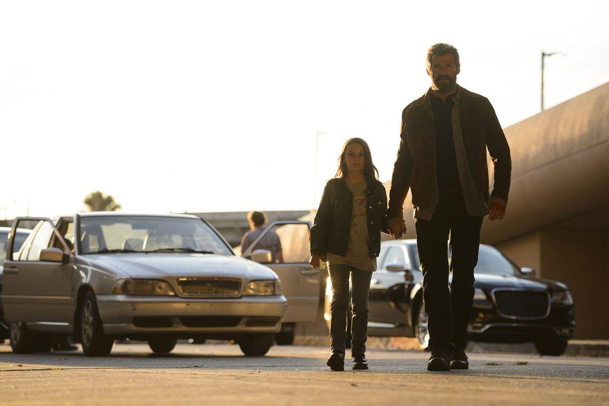 Logan (Hugh Jackman) leads Laura (Dafne Keen) by the hand.