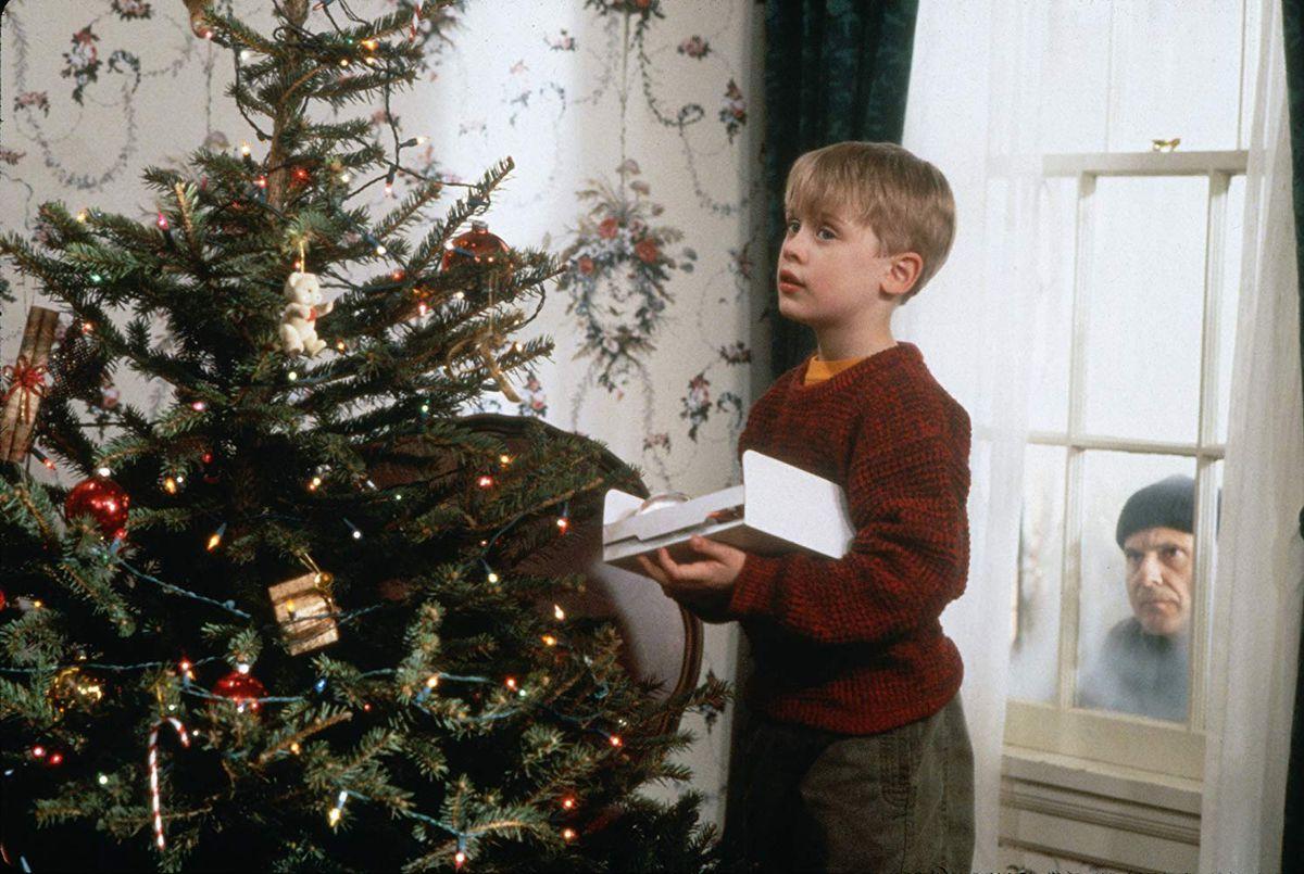 Kevin (Macaulay Culkin) decorates a tree while Harry (Joe Pesci) watches through a window.