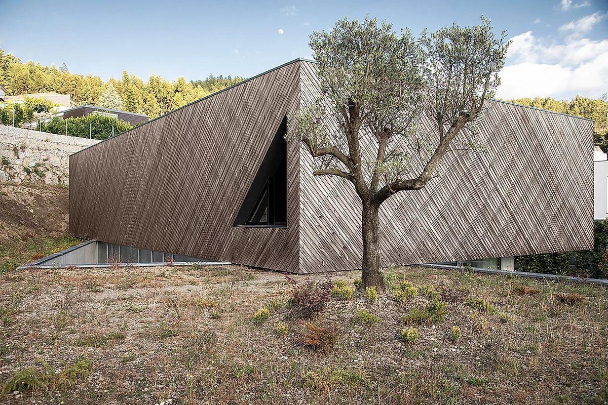 Wood clad house with triangular window.