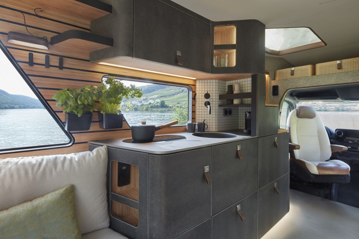 The kitchen area of the van features slate gray storage with a sink and stove on top. Bamboo slated walls hold plants.