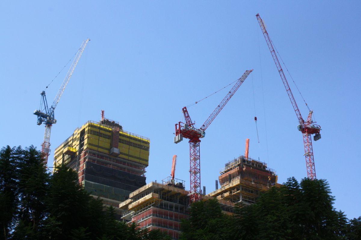 The tops of three under-construction towers and a trio of cranes.