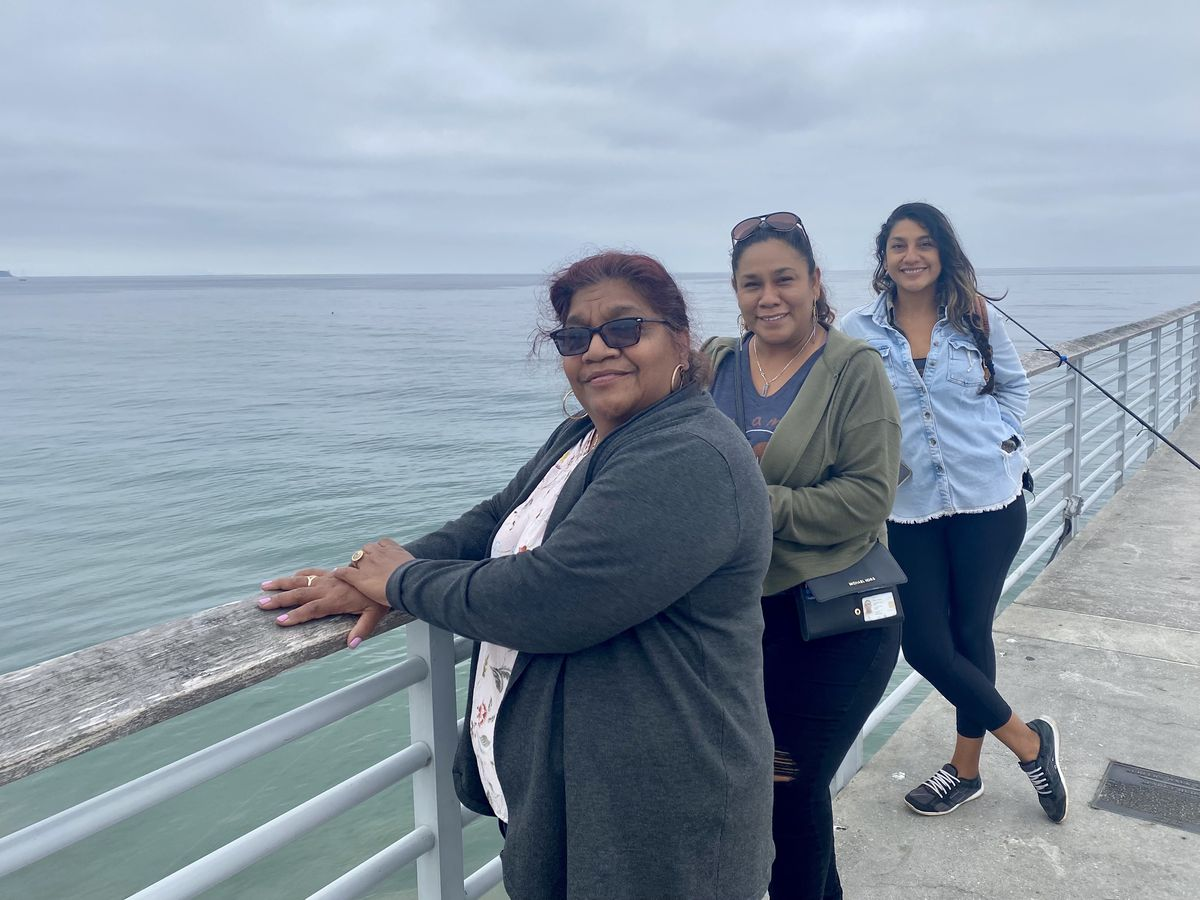 A trio of women look to a camera, backed by a cloudy sky and the endless ocean.