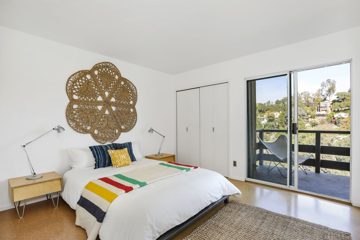 A room with wood floors and white walls. It's furnished with a bed and two small bedside tables. Sliding doors lead out to a deck.