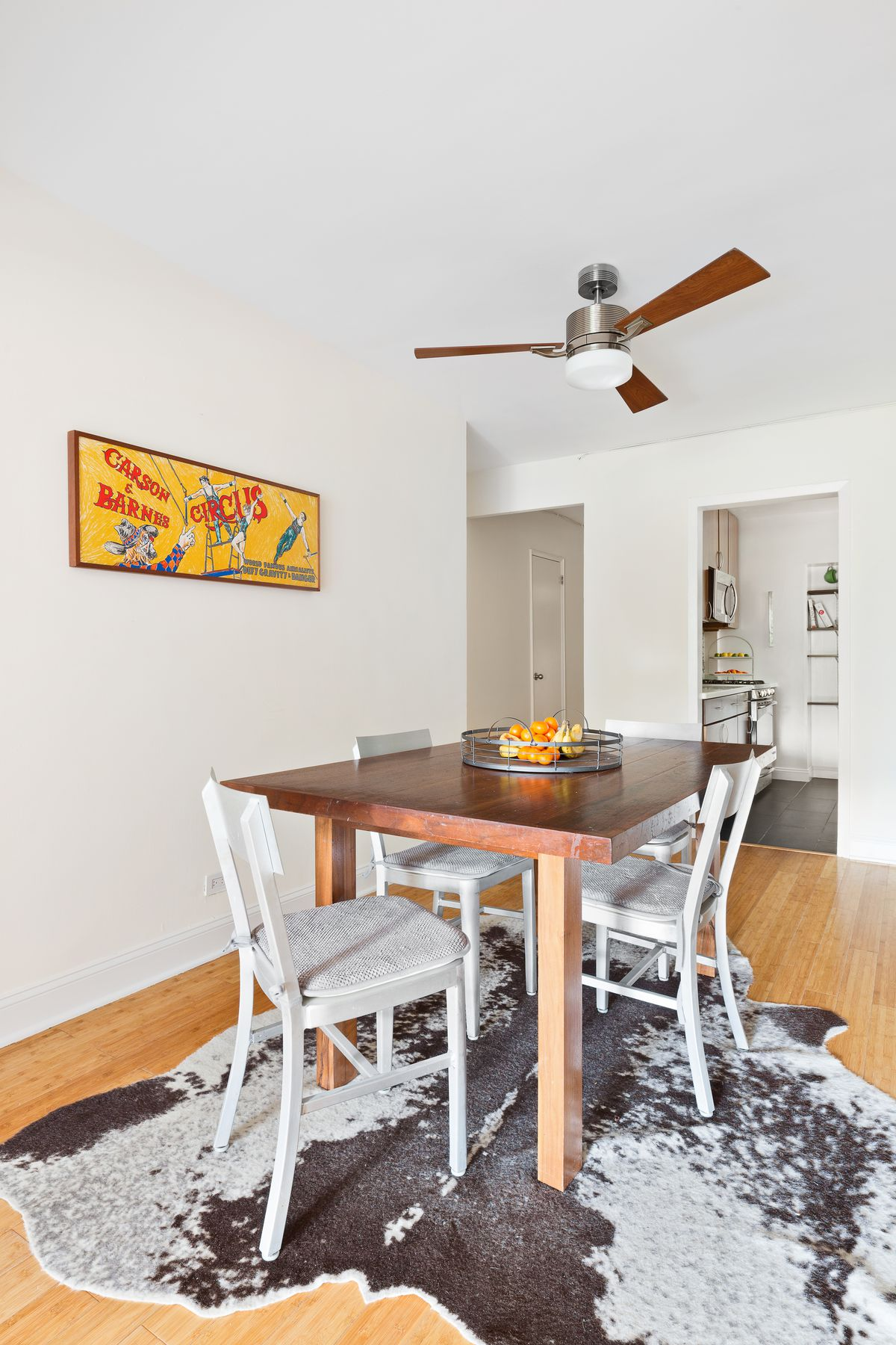 A dining area with a ceiling fan, a framed poster on the wall, a rug, a wooden table, and white chairs.